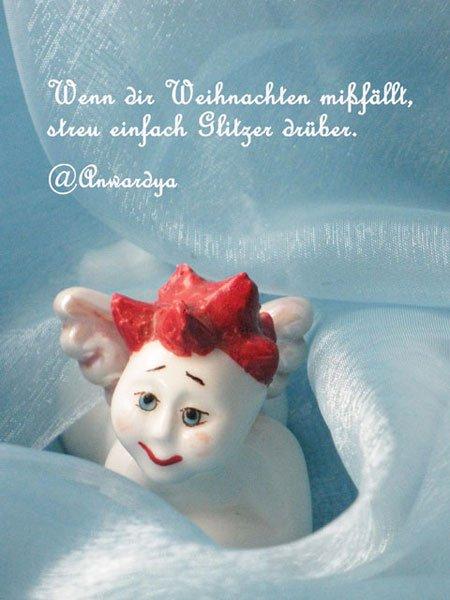 Weißes Porzellanengerl mir roten Haaren auf blauem Hintergrund und einem weihnachtlichen Tweet